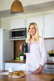 Porträt der jungen frau im schlafanzug mit französischer kaffeepresse, die in der modernen küche steht