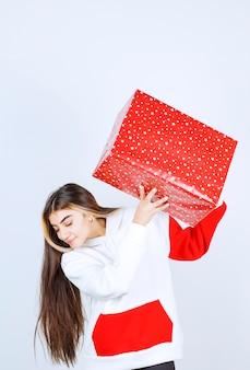 Porträt der jungen frau im warmen hoodie mit weihnachtsgeschenk