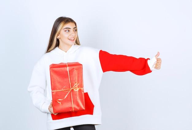 Porträt der jungen frau im warmen pullover mit weihnachtsgeschenk, das daumen nach oben zeigt