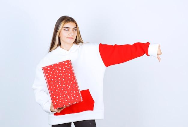 Porträt der jungen frau im warmen pullover mit weihnachtsgeschenk, das den daumen nach unten zeigt