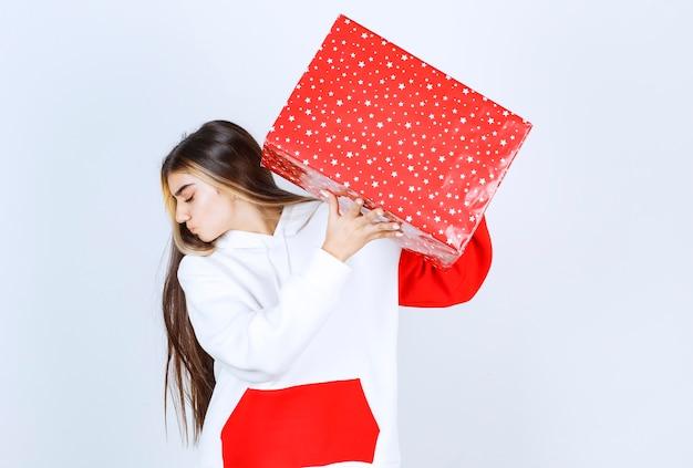 Porträt der jungen frau im warmen pullover mit weihnachtsgeschenk
