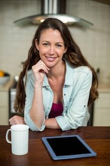 Porträt der jungen frau in der küche mit kaffeetasse und digitaler tablette auf worktop