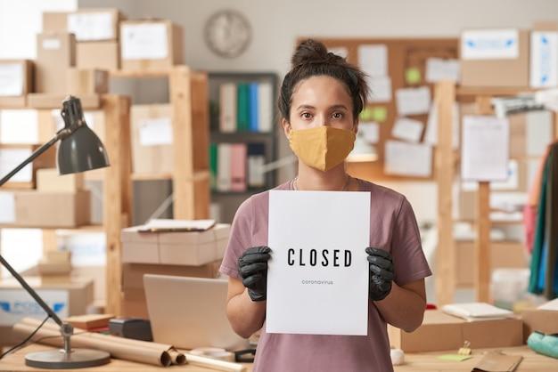 Porträt der jungen frau in der schutzmaske, die plakat in ihren händen beim stehen im büro hält