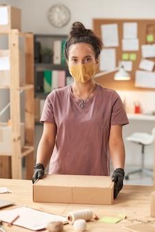 Porträt der jungen frau in der schutzmaske, die vorne beim packen des pakets für lieferung betrachtet