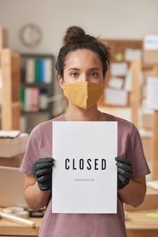 Porträt der jungen frau in der schutzmaske und in den schutzhandschuhen, die plakat halten, während sie im büro stehen