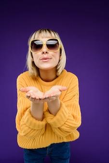 Porträt der jungen frau in der sonnenbrille über lila wand