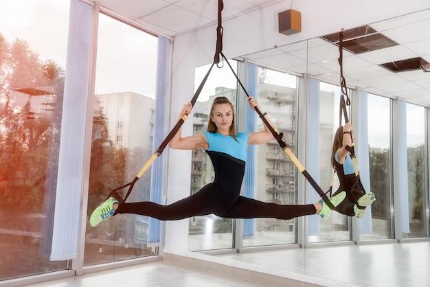 Porträt der jungen frau in der sportbekleidung, die liegestütze tut, während beine an trx im fitnessstudio hängen. mädchen, das trx-training macht