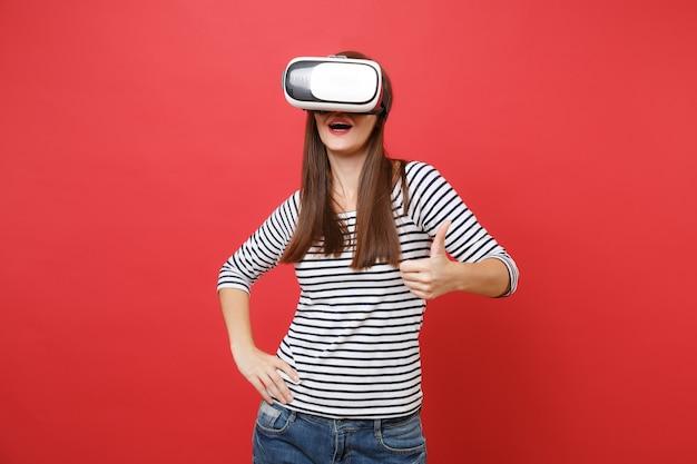 Porträt der jungen frau in gestreifter kleidung, virtual-reality-brille, die auf hellrotem wandhintergrund isoliert steht und daumen zeigt menschen aufrichtige emotionen lifestyle-konzept. kopieren sie platz.