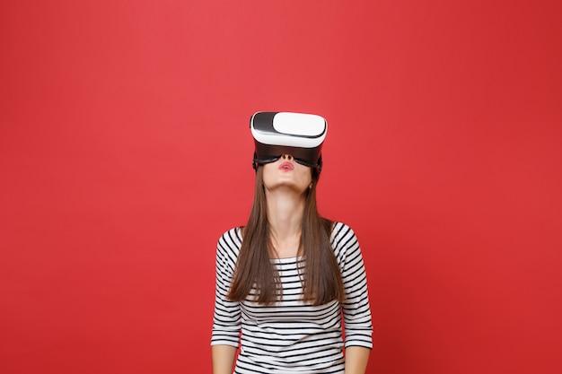 Porträt der jungen frau in legerer gestreifter kleidung, virtual-reality-brille stehend, nachschlagend auf hellrotem wandhintergrund isoliert. menschen aufrichtige emotionen, lifestyle-konzept. kopieren sie platz.