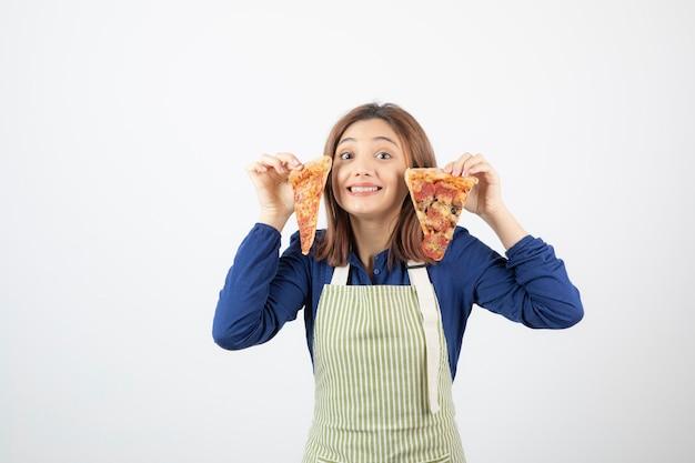 Porträt der jungen frau in schürze, die pizzastücke auf weiß zeigt
