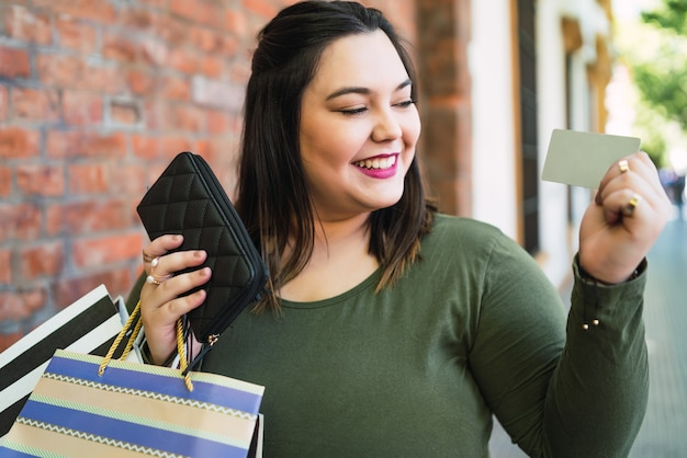 Porträt der jungen frau in übergröße, die eine kreditkarte und einkaufstaschen im freien auf der straße hält. einkaufs- und verkaufskonzept.