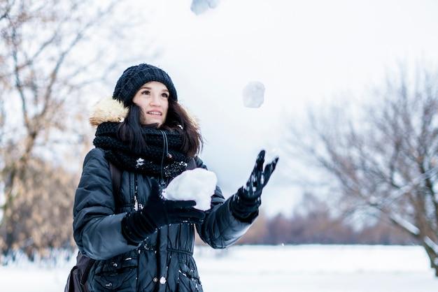 Porträt der jungen frau jonglieren mit schneebällen an einem schneebedeckten tag des winters draußen