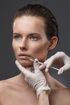 Porträt der jungen frau kosmetische einspritzung erhalten