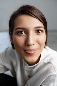 Porträt der jungen frau lächelnd, die zunge zeigt
