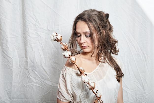 Porträt der jungen frau mit baumwollpflanze mit flauschigen blumen auf weiß