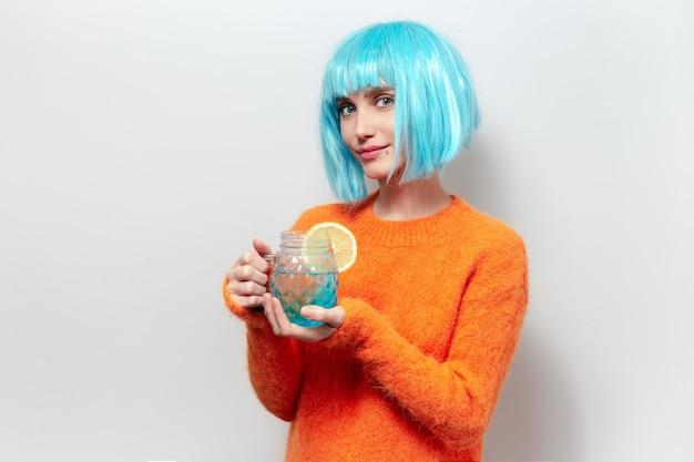 Porträt der jungen frau mit blauer bob-frisur, orangefarbenen pullover tragend, glasbecher mit saft und stück zitrone haltend.