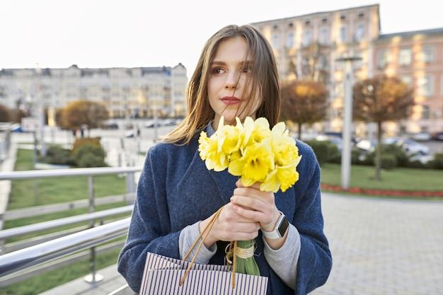 Porträt der jungen frau mit blumenstrauß von gelben narzissen