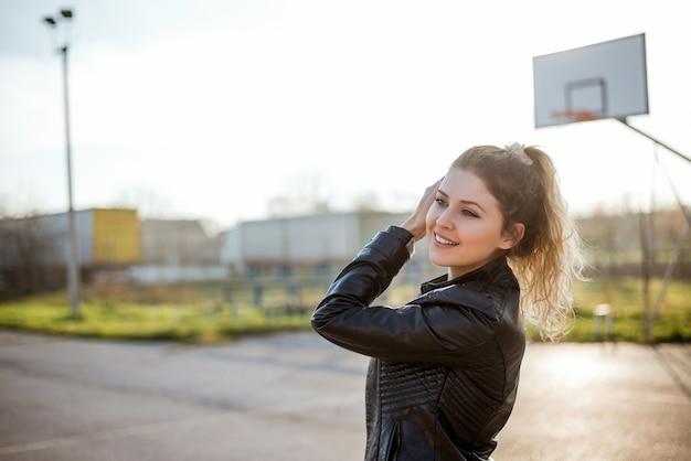 Porträt der jungen frau mit dem blonden gelockten haar draußen am sonnigen tag.