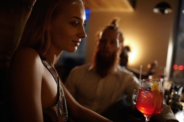 Porträt der jungen frau mit dem blonden haar, das cocktail hält