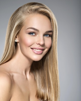 Porträt der jungen frau mit dem schönen lächeln. hübsches wunderschönes mädchen mit langen hellen glatten haaren und braunem make-up. gesicht eines modells blaue augen. posieren