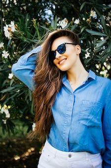 Porträt der jungen frau mit den sommersprossen und dem lockigen haar, gegen hintergrund des sommergrünparks, grüne blätter. natürliche schönheit.