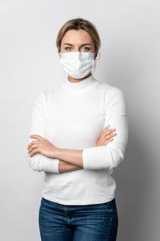 Porträt der jungen frau mit der aufstellenden chirurgischen maske