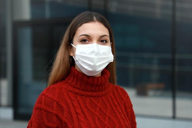Porträt der jungen frau mit der chirurgischen maske in der straße