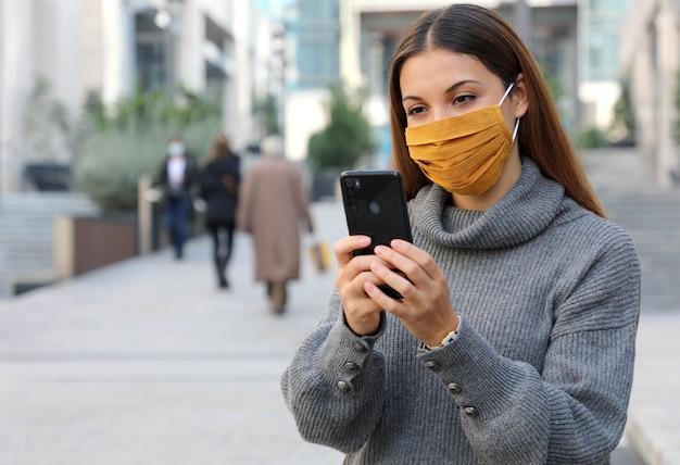 Porträt der jungen frau mit der gesichtsmaske, die draußen als sperre sitzt, öffnet hält smartphone