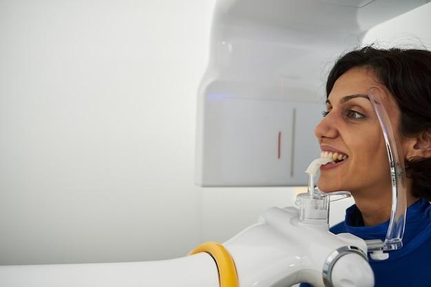 Porträt der jungen frau mit digitalem panorama-röntgenbild ihrer zähne