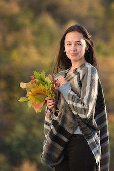 Porträt der jungen frau mit einem blumenstrauß des herbstlaubs