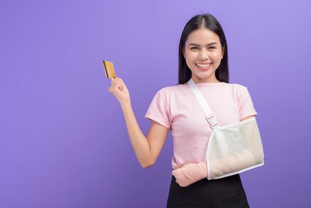 Porträt der jungen frau mit einem verletzten arm in einer schlinge, die eine kreditkarte über lila wand hält