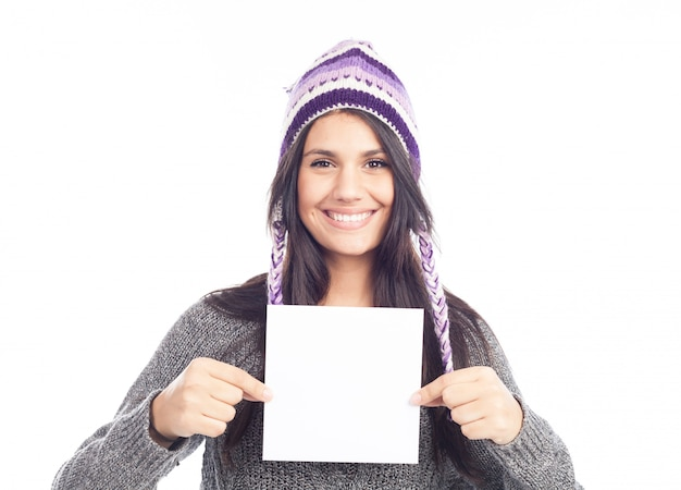 Porträt der jungen frau mit einer woolen haltenen zeichenkarte der strickjacke und des peruanischen hutes
