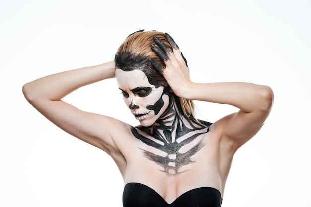 Porträt der jungen frau mit erschreckendem halloween-make-up posiert auf weißem hintergrund