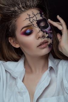 Porträt der jungen frau mit erschrockenem halloween-make-up über schwarzem