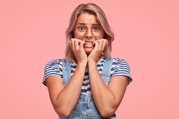 Porträt der jungen frau mit gefärbtem haar, das overalls trägt