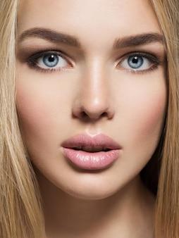 Porträt der jungen frau mit gesunder haut eines gesichts. attraktive frau mit langen, hellen, glatten haaren und braunem make-up. hübsches wunderschönes mädchen mit blauen augen - posierend