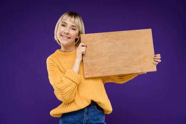 Porträt der jungen frau mit hölzernem schreibtisch über lila wand