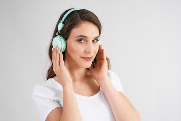 Porträt der jungen frau mit kopfhörern, die musik hören