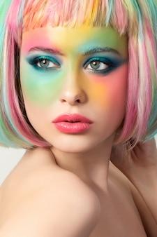 Porträt der jungen frau mit lustigem regenbogenfarbenem make-up, das ihr haar berührt