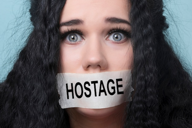 Porträt der jungen frau mit mund und lippen in klebeband versiegelt zurückgehalten und missbraucht zensiert und verboten zu sprechen, konzept der geisel