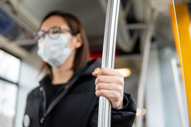 Porträt der jungen frau mit öffentlichen verkehrsmitteln mit maske