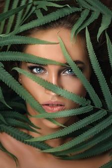 Porträt der jungen frau mit perfekter haut und blauen augen in den tropischen blättern