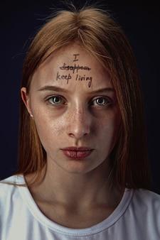 Porträt der jungen frau mit psychischen gesundheitsproblemen. das bild eines tattoos auf der stirn mit den worten, die ich verschwinde - lebe weiter.