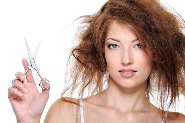 Porträt der jungen frau mit rückkämmenden haaren und mit der schere