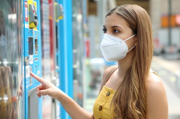 Porträt der jungen frau mit schutzmaske kn95 ffp2, die einen snack oder ein getränk am automaten im bahnhof wählt. verkaufsautomat mit mädchen.