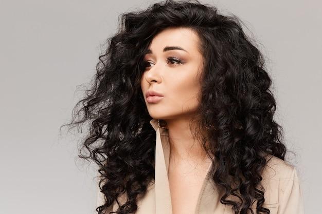 Porträt der jungen frau mit schwarzem lockigem haar und sanftem make-up am grauen hintergrund, lokalisiert mit kopienraum.