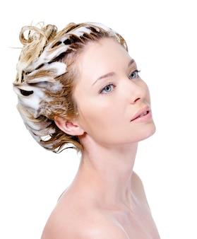 Porträt der jungen frau mit seifenkopf mit shampoo - weißer hintergrund