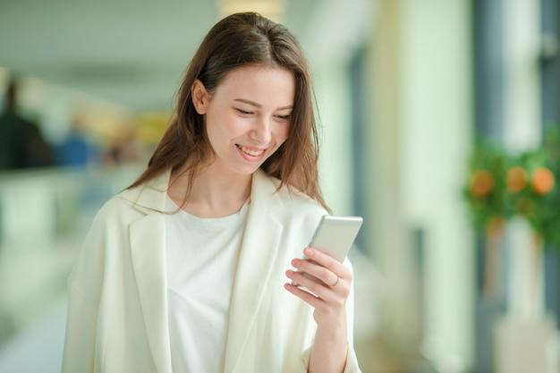 Porträt der jungen frau mit smartphone im internationalen flughafen. fluggast in einem flughafenaufenthaltsraum, der auf flugflugzeuge wartet