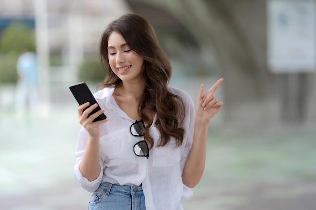 Porträt der jungen frau mit smiley-gesicht unter verwendung eines telefons geht in einer stadt