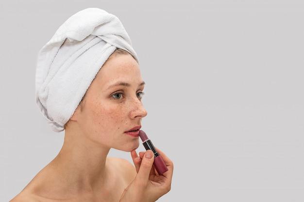 Porträt der jungen frau mit sommersprossen steht und hält lippenstift nah an lippen. sie ist ernst und konzentriert. model trägt ein weißes handtuch um ihr haar.